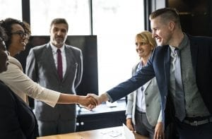 Man and Woman shaking hands in business deal with other man and other woman looking on