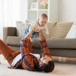 Happy Father with baby boy at home in living room by sofa