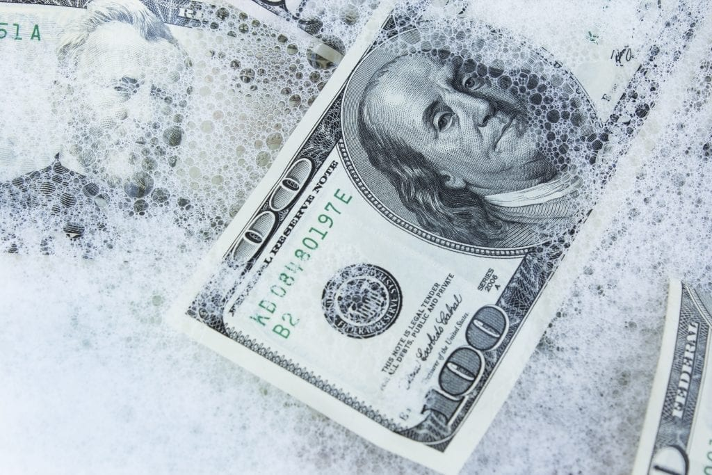 An US 100-dollar bill floats in soapy water